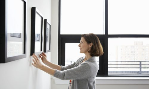Woman, in her 40's, hanging picture in her apartment, straightening it to get it